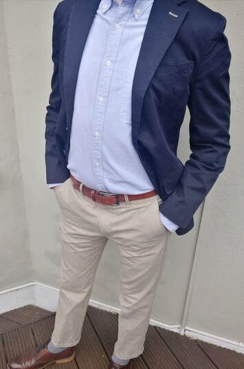 Man wearing a navy blazer, blue Oxford shirt and chinos
