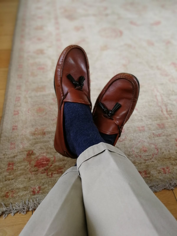 Brown leather loafers with  beige chinos and navy socks